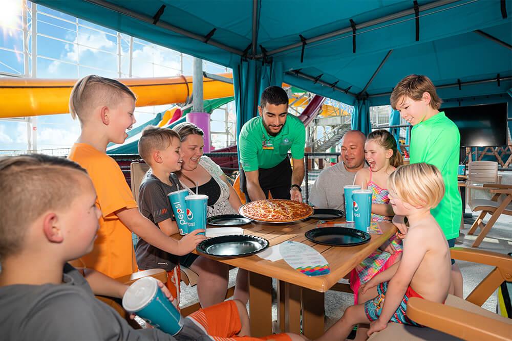 Kids enjoying pizza in cabana